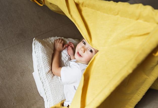 Une belle fille en pantalon jaune et un t-shirt blanc sourit et joue à l'intérieur du tipi à la maison sur le canapé. jeux à domicile pour enfants