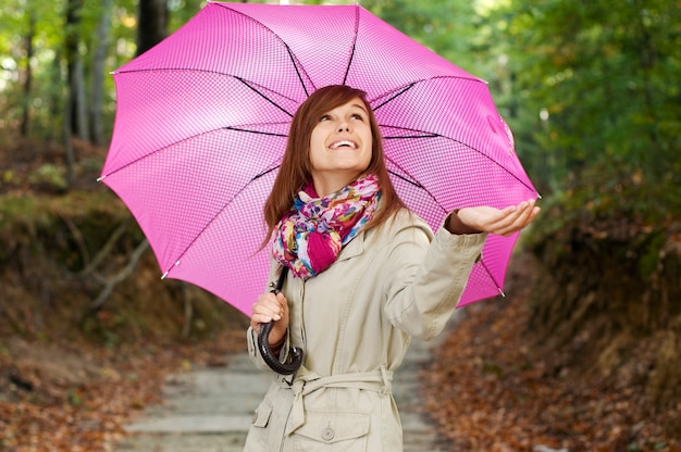 Belle fille avec parapluie vérifiant la pluie