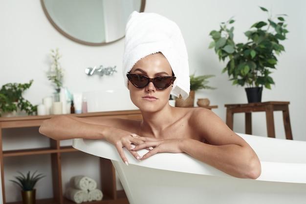 La belle fille pathétique avec vitiligo se trouve dans le bain dans les lunettes de soleil du chat et une serviette sur la tête. le concept de la mode, des soins de la peau et du style.