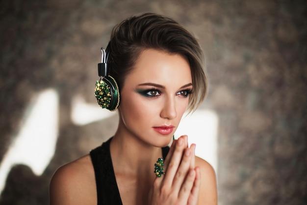Belle fille avec une peau bronzée et des cheveux blancs écoutant de la musique sur un casque. portrait de la beauté féminine d'un beau maquillage. profiter de la bonne musique
