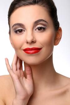 Belle fille avec une peau parfaite et rouge à lèvres