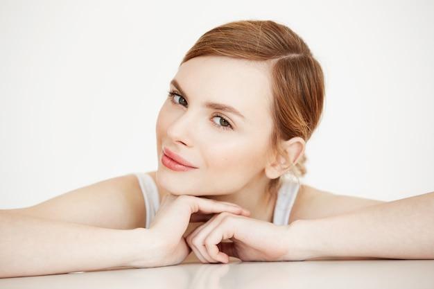 Belle fille avec une peau parfaitement propre souriant assis à table. spa de beauté et cosmétologie.