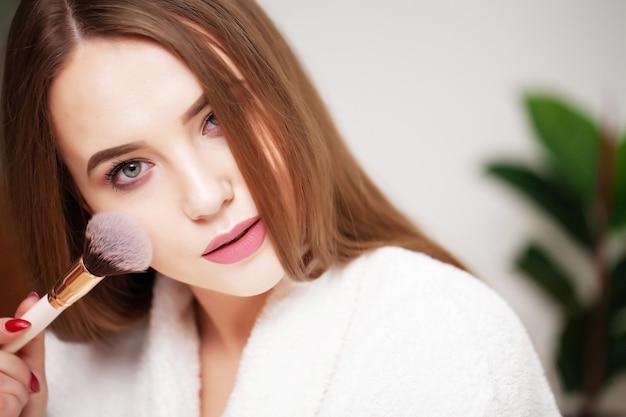 Belle fille avec une peau saine se maquiller