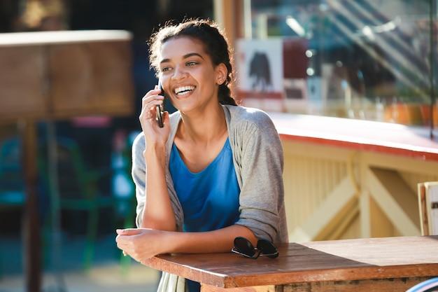 Belle fille à la peau sombre joyeuse a parlé au téléphone