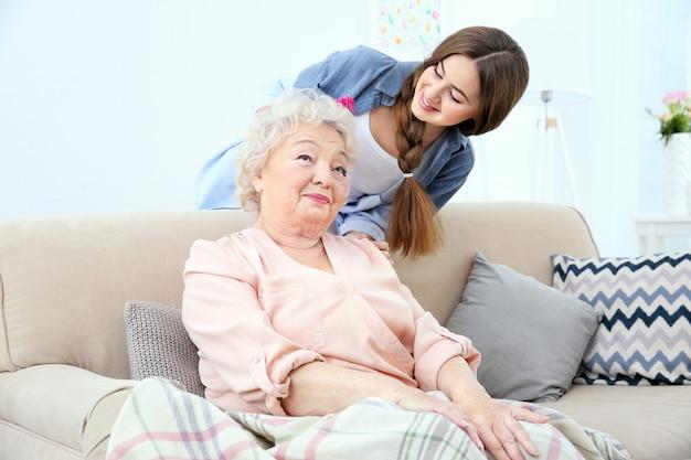Belle fille peignant les cheveux de grand-mère à la maison