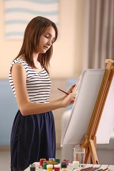 Belle fille peignant sur toile dans la chambre