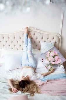 Belle fille peintre sur le lit dans sa chambre admire la photo qu'elle a dessinée