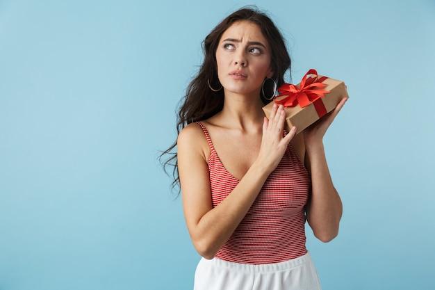 Belle fille pensive portant des vêtements d'été debout isolé sur bleu, tenant une boîte-cadeau