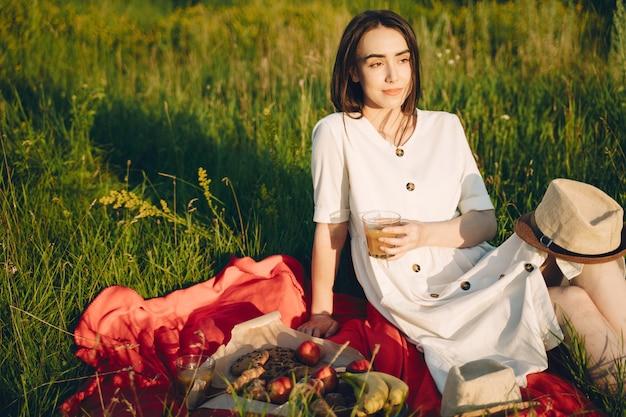 Belle fille sur un pique-nique dans un champ d'été