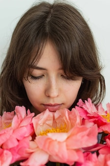 Belle fille avec des pivoines roses se bouchent, joyeux anniversaire ou saint valentin