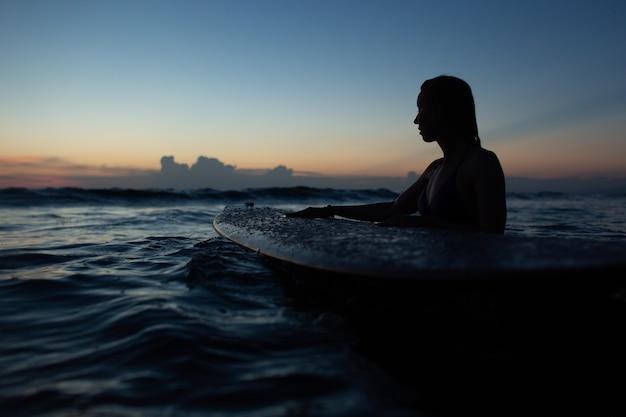 Belle fille avec une planche de surf au coucher du soleil