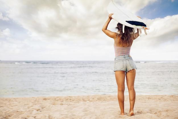 Belle fille sur une planche de surf dans l'océan