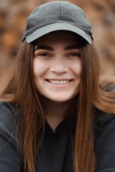 Belle fille portant un t-shirt décontracté sur fond marron regardant la caméra avec le sourire sur le visage, expression naturelle.