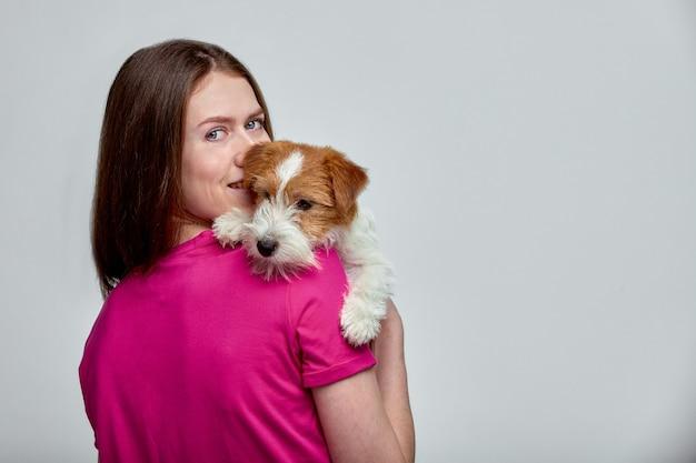 Belle fille portant un t-shirt rose avec un jack russell terrier sur ses mains sur un motif gris, espace copie