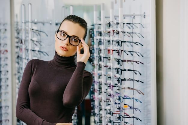 Belle fille porte des lunettes dans un magasin d'opticien.