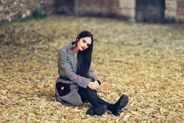 Belle fille porte manteau d'hiver assis sur le sol d'un parc urbain plein de feuilles d'automne.
