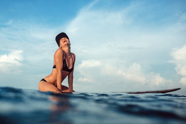 Belle fille posant assis sur une planche de surf dans l'océan