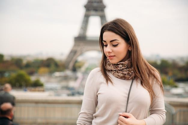 Belle fille posant au photographe dans le contexte de la tour eiffel. l'automne
