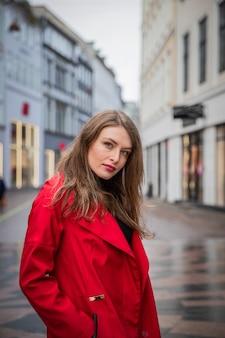 Belle fille posant dans le centre-ville vêtue d'un manteau rouge.belle fille posant dans le centre-ville vêtue d'un manteau rouge. le modèle se promène dans les rues de la ville.