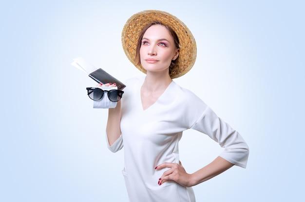 Belle fille posant sur un fond blanc dans un chapeau jaune. elle a un masque médical dans les mains. le concept de tourisme pendant l'épidémie. technique mixte