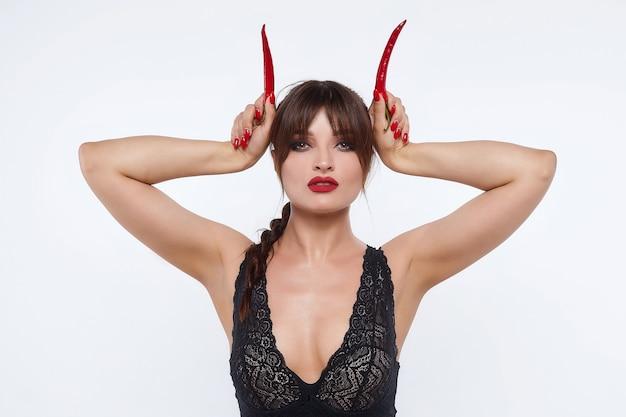 Belle fille posant avec des piments rouges