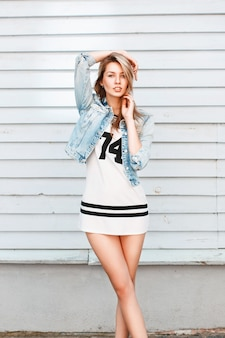 Belle fille posant près d'un mur en bois blanc à la plage