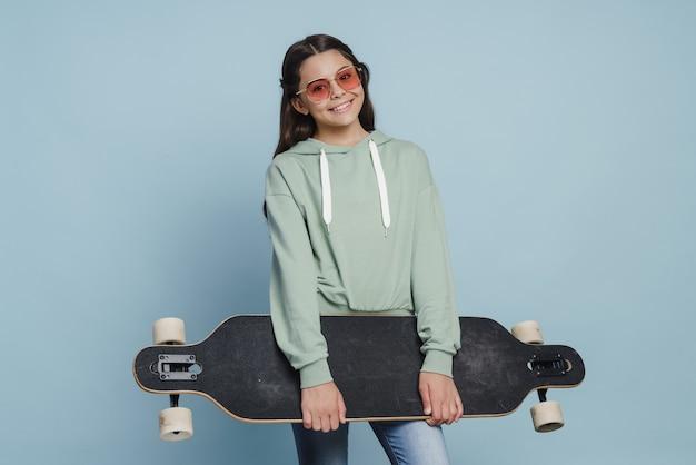 Belle fille positive à lunettes de soleil tenant un patin dans ses mains. adolescent mignon sur fond bleu