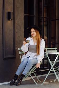 Belle fille prenant un café au café