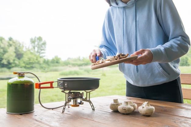 Belle fille prépare la nourriture dans le camping dans la cuisine touristique avec un brûleur à gaz et une bouteille
