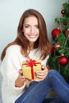 Belle fille près de l'arbre de noël avec cadeau