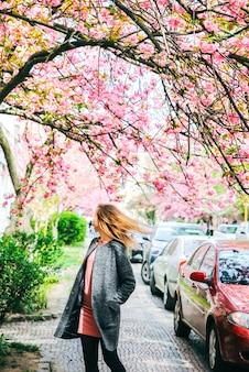 Belle fille près des arbres de sakura. femme en robe et manteau élégant fleurs roses qui fleurissent à oujhorod. fleurir autour. temps de printemps. concept de détente et de bonheur.