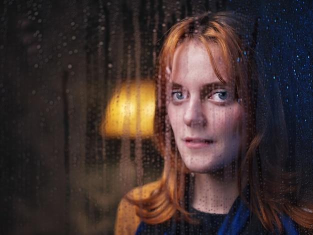 Belle fille près de la fenêtre pluvieuse