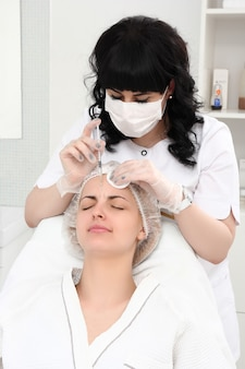Belle fille sur une procédure de rajeunissement en clinique de beauté