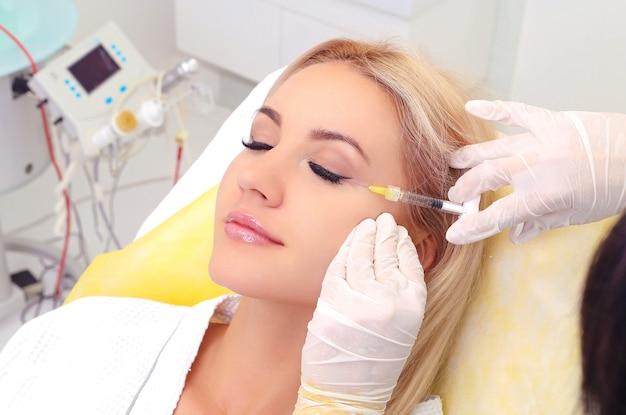 Belle fille sur la procédure de rajeunissement en injection de remplissage de clinique de beauté
