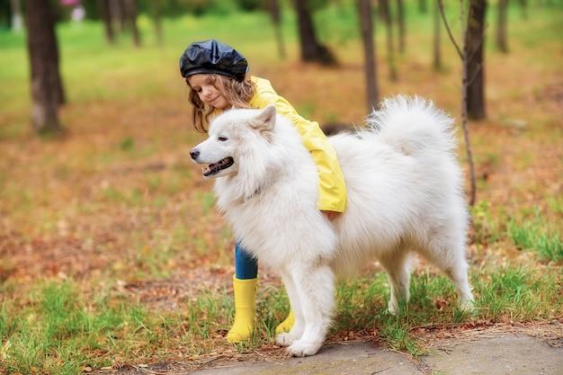 Belle fille sur une promenade avec un beau chien dans un parc en plein air