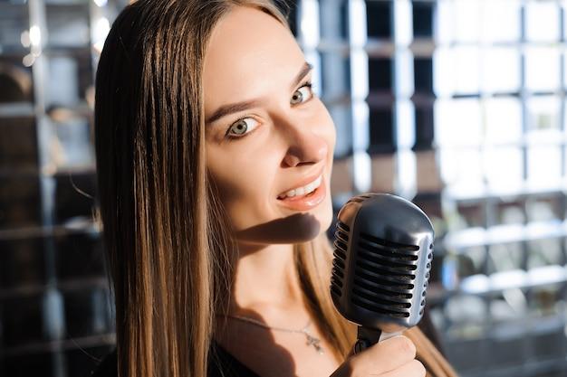 Belle fille qui chante. beauté femme avec microphone