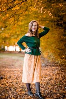 Belle fille qui marche à l'extérieur à l'automne. fille souriante recueille les feuilles jaunes à l'automne.