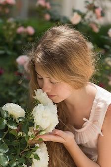Belle fille qui sent, tenant des fleurs en robe rose à l'extérieur pendant la journée.