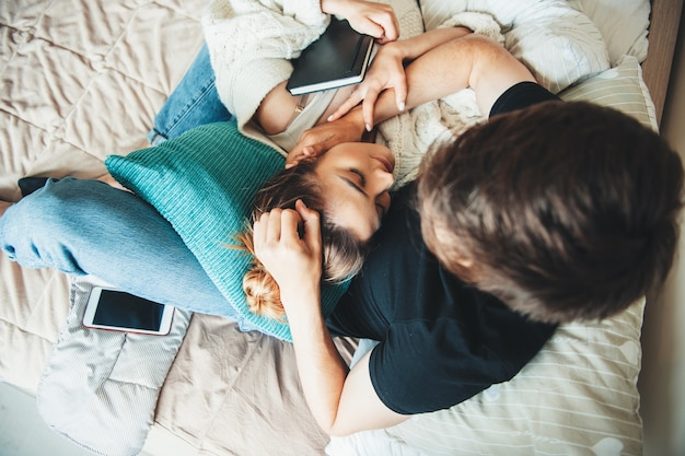 Belle fille de race blanche aux cheveux bruns allongée sur son petit ami dans le lit recouvert d'une couette et tenant un livre