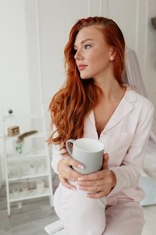 Belle fille de race blanche avec une femme aux cheveux rouges portant un pyjama rose tenant une tasse de café le matin