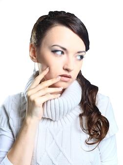 Belle fille réfléchie en pull. isolé sur fond blanc.