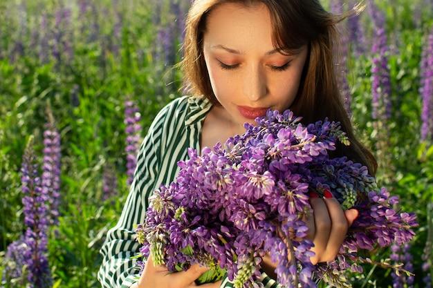 Belle fille regardant une brassée de lupin sur champ fleuri