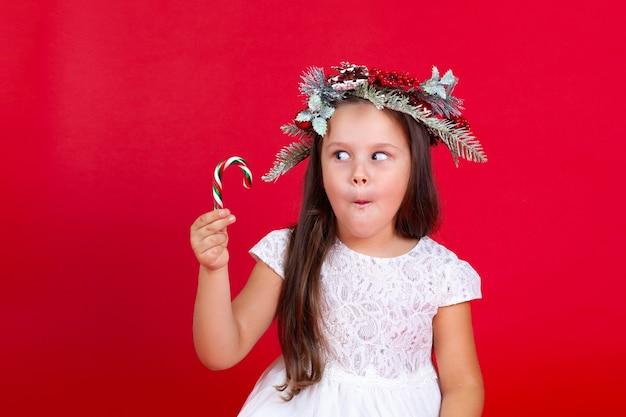 Belle fille regardant avec surprise une canne au caramel
