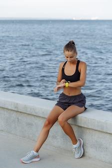 Belle fille de remise en forme avec une montre de sport assise au bord de la mer