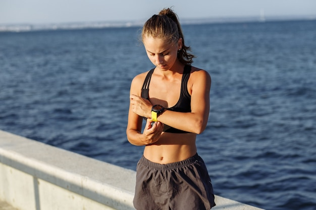 Belle fille de remise en forme porte une montre intelligente avant de courir au bord de la mer