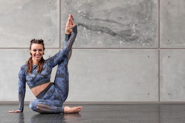 Belle fille de remise en forme sportive avec des nattes est assise sur le sol avec sa jambe levée. le sourire est engagé dans le yoga. survêtement bleu camouflage. sport et santé