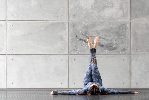 Belle fille de remise en forme sportive avec des nattes. faire du yoga. se trouve avec les jambes levées sur le fond d'un mur de pierre grise. survêtement bleu camouflage. espace libre pour le texte. sport et santé