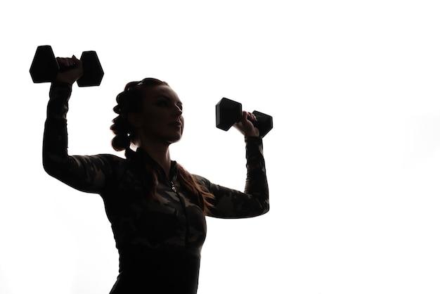 Belle fille de remise en forme sportive avec des nattes en haltères dans ses mains. prise de vue contour, à l'ombre. sport et santé