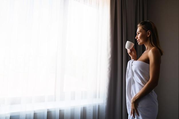 Belle fille reste près de la fenêtre enveloppée d'une serviette blanche, savoure un verre dans une petite tasse.