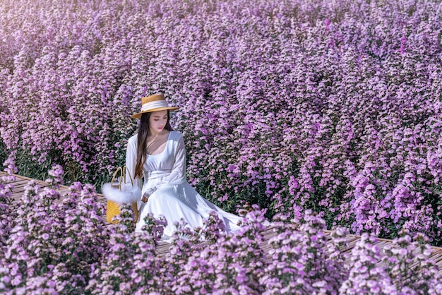 Belle fille en robe blanche assise dans les champs de fleurs de margaret